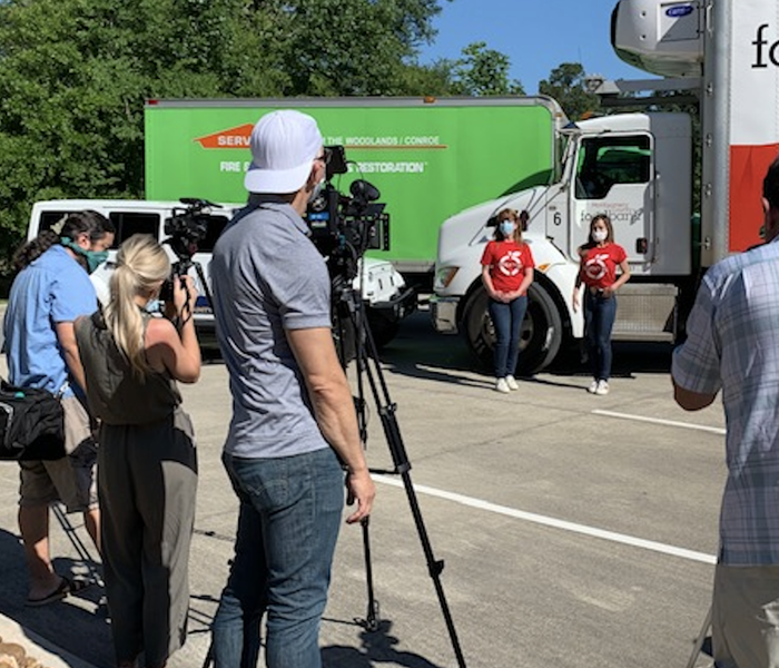 people standing in front of a white and red truck and a SERVPRO truck